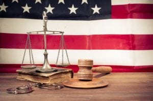 Law scales, judge gavel, handcuff, old book front USA flag